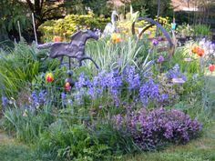 Spring bluebells, orange tulips and heather sprawl beneath Winston, my old weathervane from P.E.I. #horseweathervane