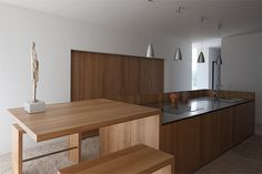 cocina de isla central para fregadero y zona de cocción con barra, módulos empotrados y suelo de piedra