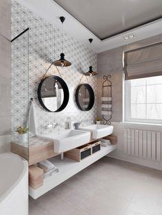 Łazienka wypełniona jest charakterystycznymi dodatkami. Oprócz luster w czarnych ramach są to także dwie wiszące lampy...