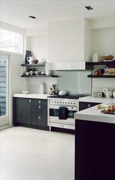 Köket, designat av Piet Boon, har skåp i ek som färgats för att likna wenge. Rummet har ett betongli...