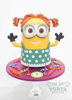 "This is Minion Dave as you've never seen him before.............wearing a dress! This fun cake was made for a little girl turning two today who is obsessed with Minion Dave but her mum wanted something a little more girly, so after some googling, I managed to find some ""fan art"" online of Minion Stu in this get up, so I copied it but made it Dave instead. This minion is standing and the finished height is about 11"". Strawberries and cream cake inside covered with white ..."