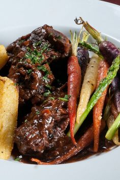 Recipe including course(s): Entrée; and ingredients: beef broth, brown sugar, butter, chili powder, chili sauce, flour, garlic, ketchup, onion, pepper, red wine vinegar, salt, short ribs, Worcestershire sauce
