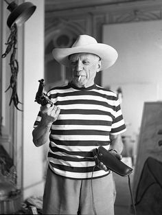 Pablo Picasso with Gary Cooper's gun and hat in 1959, a moment captured by photographer André Villers.