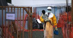 Un'operatore di Medici Senza Frontiere con un bambino sospettato di aver contratto l'ebola.