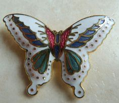 A pretty vintage enamel butterfly brooch. The brooch design is of a white butterfly with red, green, blue and gold detailing to the wings set in gold tone metal.  Vintage circa 1970's - 80's