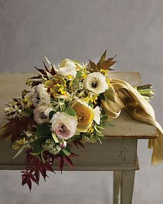 Japanese maple twigs frame a painterly bouquet of gold tree peonies, yellow kangaroo paws, pink ranunculus, and ivory astilbe.