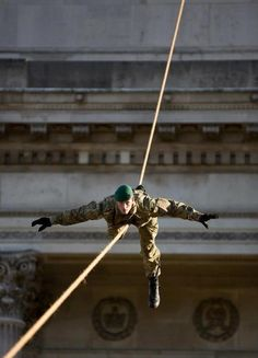 Royal Marine Commando Tom Senior descends on a zip wire from Wellington Arch, London.