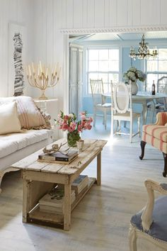 Gorgeous rustic white living room with blue dining room beyond.