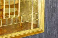 Mirror with antiqued glass set in brass stepped frame with geometric fretwork details.
