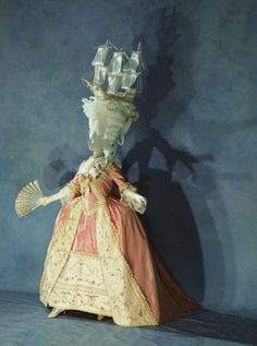 """Dress (""""robe à la française"""") c. 1780- France. This dress, with its dynamic silhouette, shows a peak of women's court dress in the latter part of the 18th century. The skirt, which widely expanded on each side, just barely achieves balance when combined with the enormous hairstyle. This pinnacle of artificial beauty emptily expressed the authority of the royalty and nobility before French revolution."""