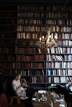 OMG, I want that chandelier in my own library , and those dark wood shelves are beautiful!