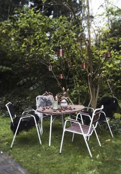 Lovely dining space in the garden with modern garden furniture and fine lanterns in the trees.