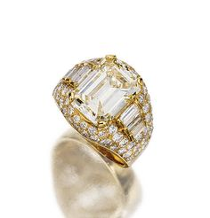 FANCY LIGHT YELLOW DIAMOND RING, 'TROMBINO', BULGARI, 1980S.  The fancy light yellow step-cut diamond weighing 9.12 carats flanked by stepped baguette stones, within a bombé frame of pavé-set brilliant-cut diamonds, mounted in yellow gold, size 62, signed Bulgari.