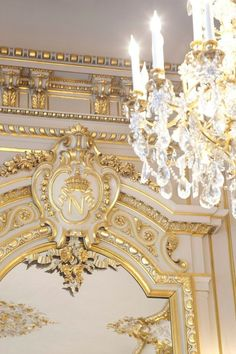 Perfection. Chandelier with golden details, and golden embellished mirror with initial.