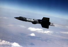 a rare historic picture of the black missile-shaped hypersonic speed X-15 experimental aircraft in flight, seen from left, high over the Mojave Desert,