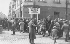 """Jewish policemen and German soldiers regulate movement of residents in the ghetto of Lodz. The inscription on the tag: """"A residential area for Jews. Off limits. """""""