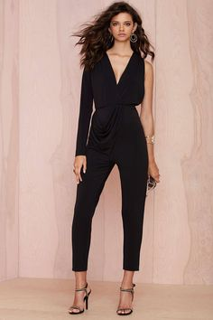 When you hit the town, arrive in one-piece. The Molten Jumpsuit is made in a stretchy black matte crepe jersey and features asymmetrical sleeveless design, plunging v-neckline, gathering detail, and asymmetrical drape embellishment at waist. Unlined. Perfect with heels and a vampy pout