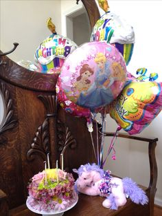 Flower birthday cake, balloons and plush.