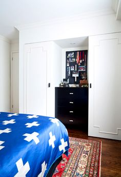 White closet doors, black drawers, blue bedding with white crosses, and black bulletin board