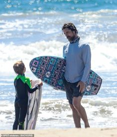 Showing his son the ways of bodyboarding: Christian Bale was seen sporting a shaggy beard ...
