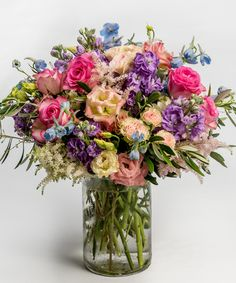 Summer Sunset This gardeny design of beautiful purples, lavenders, pinks and blues - including roses, lisianthus, and delphinium - is sure to bring the warmth of summer into any home.