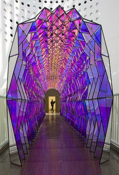 One Way Colour Tunnel by Olafur Eliasson. This is a tunnel made up of light-shattering translucent and reflective triangular panels of coated acrylic, resembling a walkway of stained glass. It can appear monochromatic from one angle or multi-colored from another angle. This is at the San Francisco Museum of Modern Art.