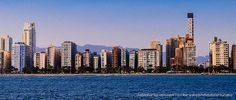 Vista da orla de Santos à partir do mar, de onde podem ser observados alguns edifícios com inclinação acentuada. Uns para a esquerda e outros para a direita.