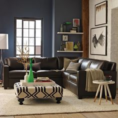 Love the brown leather sectional with the blue accent wall and black and white ottoman.