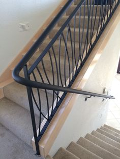 """Custom residential wall mount stair rail system with """"Long Grass"""" design, powder coat finish and splice lock for an almost seamless aesthetic."""