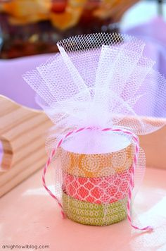 tea light candles wrapped with washi tape and packaged in tulle circles tied with baker's twine. (Chocolate Regalo Wedding Favors)