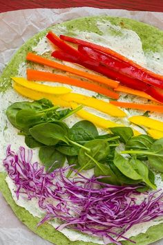 A spinach tortilla with layers of rainbow colored veggies.
