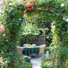 Ein Rosenbogen und Sichtschutzzaun machen den kleinen Sitzplatz zu einem behaglichen Wohlfühlraum
