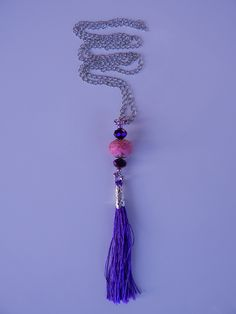Long silver nacklace made of a pink #stone bead, #glassbeads and purple thread #tassels. Very uniq and brave combination. www.ayaglass.hu