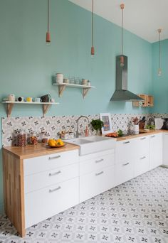 I'd probably continue the tile all the way up the wall behind the sink and cooktop. As it stands, the vent hood and shelves look a bit orphaned. But I do like the teal accent. It could go on sidewalls where there is less kitchen mess. I might also invert the cabinets and counters (crisp white counters with lighter wood cabinets). But I like the material palette here.