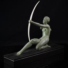 """DESCRIPTION: Art deco bronze sculpture of a woman laying back while aiming a bow comprised of bone. Finished with a green patina and rests on a black marble base. Signed """"Oudine"""" CIRCA:19th Ct.ORIGIN: France DIMENSIONS: H: 11"""" L: 18.5""""  W: 4.75"""""""