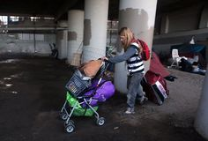 Jensina Hardig, 35 years old, leaves the homeless encampment beneath the Interstate 280 on-ramp in San Francisco, Calif., on Monday, March 11, 2013. The encampment was forced to leave this morning with a permanent fence planned to keep the camp out of the area.
