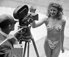 """The new """"Bikini"""" swimsuit in a newsprint pattern caused a sensation at the Molitor swimming pool in Paris (July 5, 1946). Designer Louis Reard was unable to find a """"respectable"""" model so the job of wearing it went to Micheline Bernardini, a nude dancer from the Casino de Paris. She is holding a box into which the garment can be packed. Celebrated as the first bikini, Luard's came a few months after a similar two-piece design was made by Jacques Heim."""