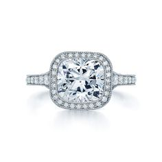 A diamond ring in platinum with a cushion shape diamond center stone in the Kwiat signature floating basket, a pave diamond frame and a band with hand-engraving.