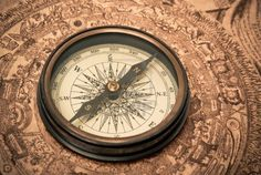 Antique compass lying on old style map. Sepia toned. Stock Photo - 9356770
