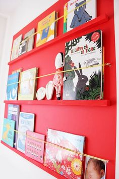 Easy, affordable way to display books as well as creating an ever changing wall art space. The red background is a painted wall. Add some grooved wood molding painted same colour as wall. Attach some stretchy bungee rope secured to wall with hooks and it's done. This is a great space saving idea, when book shelves are not possible. Even a hallway could accommodate this clever reading area.