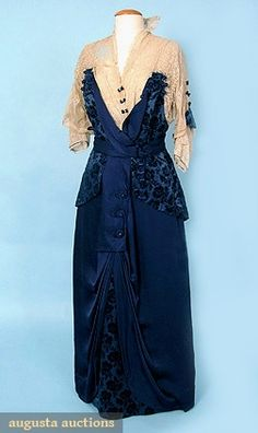 """VELVET & LACE TEA GOWN, c. 1914. Lot: 805 October 2006 Vintage Clothing & Textile Auction, New Hope, PA.   Midnight blue cut velvet & blue silk satin gown w/ cream lace bodice, trimmed w/ tiny velvet & rhinestone bows & beaded ball tassels, B 34""""; W 28""""; H 45""""; Gown L 58""""; Hem C 68"""", excellent.      Price Realized: $ 862.50      Category: Womens      Era: 1890-1920      Condition: Excellent"""
