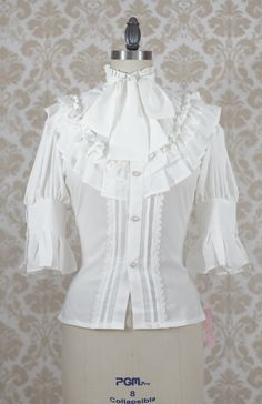 Designed and Manufactured by Souffle Song in China, this blouse features a high collar with soft ruffles and a removable bow tie. There is beautiful button detailing on the cuffs which match the buttons on the front. The corset ties on the back allow you to adjust the blouse to optimal fitting fo...