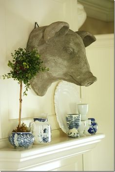 topiaries and a gray piggie turn a hanging shelf into a gorgeous focal point