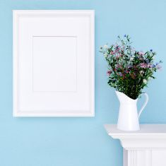 Mock up poster and wildflowers on a blue wall stock photo