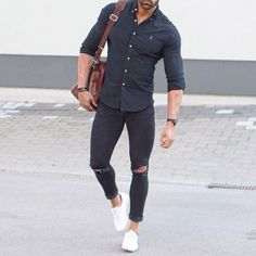 Bolso marrón, camisa entallada azul oscuro, y pantalones chupín cortados con zapatillas blancas