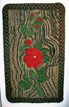 WALDOBORO TYPE HOOKED RUG ON A VARIGATED GROUND WITH A BRAIDED BORDER.  New England, Late 19th century.