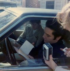 Elvis (with Jerry Schilling in the passenger seat), wearing a black turtleneck…