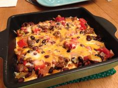Tortilla Black Bean Casserole - Made with onion, bell pepper, chopped tomatoes, prepared salsa, garlic, cumin, black beans and Monterey Jack cheese.  Top with tomato, lettuce, black olives and sour cream.  Delicious!