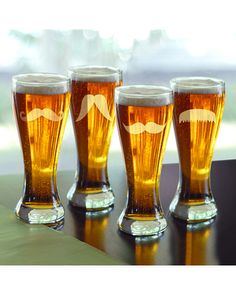 Gentleman's Mustache Pilsner Beer Glasses - Set of This set of four pilsner beer glasses is sure to be a hilarious hit in your glassware cabinet. Each glass is carefully hand blown and features a different mustache design etched onto its surface.