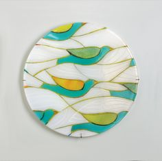 Migration by Lynn Latimer. Cheerful birds fly across a fused glass wall panel full of graceful, flowing lines and intricate pattern. The vibrant colors and iridescent surface make it a beautiful addition to any room - it requires no backlighting to look extraordinary. Wings are individually patterned by the artist and will vary. Custom metal hanger included.